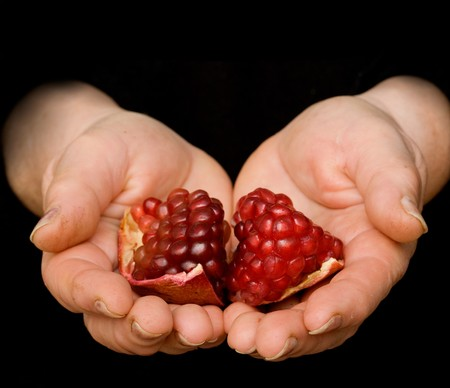 superfruit: pomegranate in hand isolated on white background