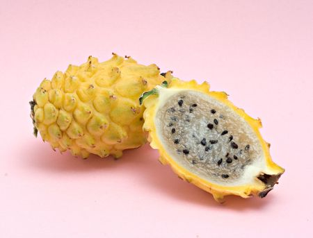 Yellow dragon fruit and its section isolated on pink background photo