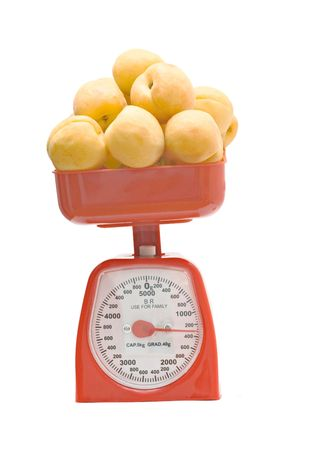 weighting: Red kitchen scale weighting apricots Stock Photo
