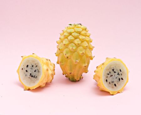 Yellow dragon fruit and its sections isolated on pink background photo
