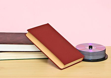 rewritable: Pile of books  and DVD disk as symbols of old and new methods of information storage