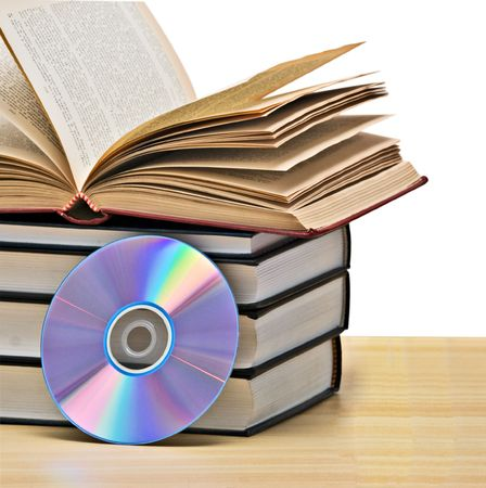 Pile of books  and DVD disk as symbols of old and new methods of information storage photo