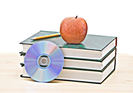 Apple, dvd, and books as a symbol of transition from old to new ways of learning photo