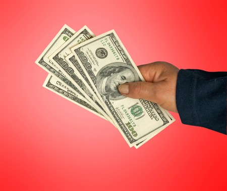 creditor: Hand with dollar bills isolated on background