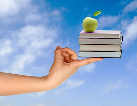 Books with apple on finger as a gift of education Stock Photo - 8550646