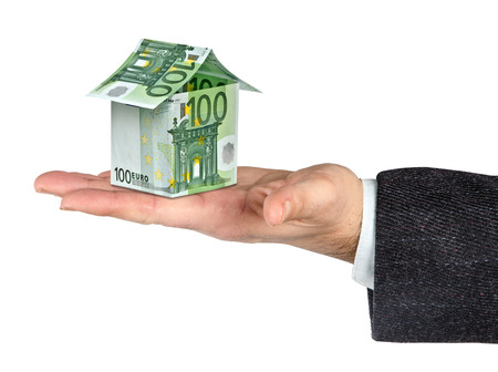 dweling: Money home and hand isolated on white background