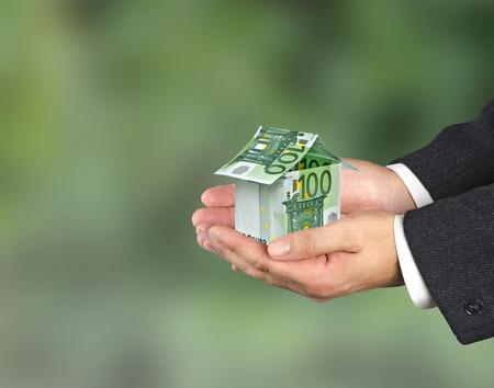 Casa denaro e mano isolato su sfondo bianco Archivio Fotografico