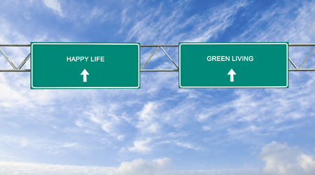 green living: Road sign to happy life and green living Stock Photo