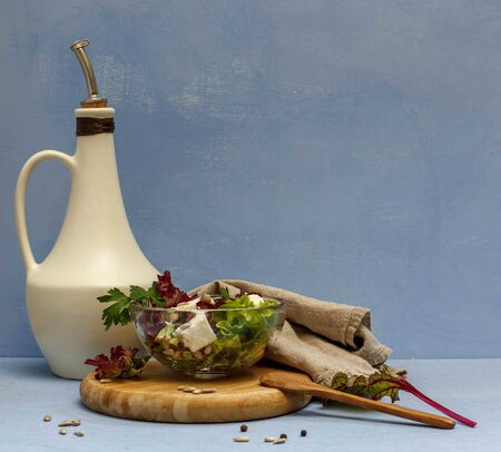 lettuce with cottage cheese and seeds in a glass bowl and a white jug on a blue background, space Banco de Imagens