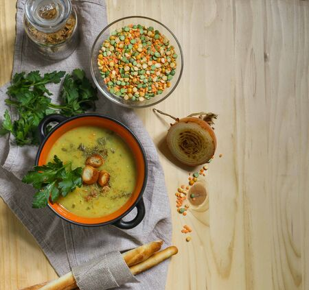vegan cream pea and lentil soup in black pot with croutons and parsley on a linen table napkin, with breadsticks on a wooden table, top view Standard-Bild