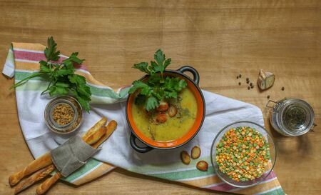 cream soup of different varieties of peas and lentils with croutons and parsley in a black saucepan on a linen towel with bread sticks on a wooden surface, top view