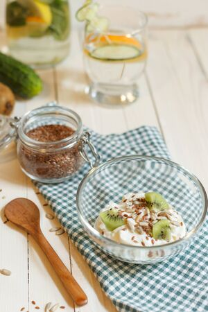 White wooden table with Breakfast. Yogurt with flax and sunflower seeds , kiwi slices and a glass of Sassi water on a checkered green napkin, vertically Фото со стока