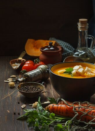 pumpkin soup with crackers and parsley in a black bowl and fresh carrots in a string bag on the kitchen wooden table, with fresh vegetables, oil and a vintage pepper mill