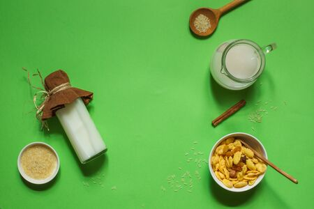 flatlay on a bright green background with a bottle of rice milk, corn flakes and a jug with space