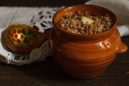 Buckwheat porridge in a brown ceramic pot with a piece of butter and a wooden painted spoon on a linen napkin, blurred background 版權商用圖片