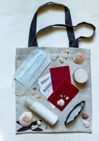 Travel documents, sunglasses and protective mask on a beach bag with leisure accessories on white