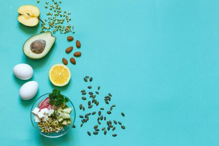 Munga bean sprouts, avocado, eggs, tofu, seeds, nuts on aquamarine