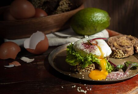 Sandwich with a poached egg cut on a copper plate, low key with space Stok Fotoğraf