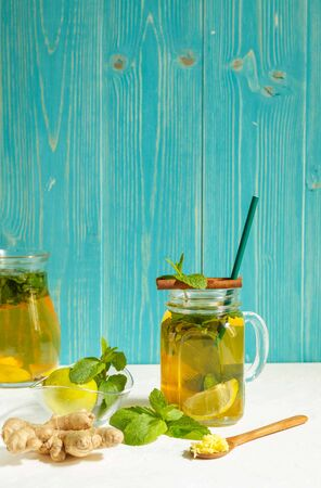 Delicious cocktail for detox diet with ginger, cinnamon, lime and mint, in a glass Cup with a paper tube ingredients for cooking, on an aquamarine wooden background, vertically with space