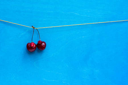 a pair of funny cherries of non-standard shape on a rope, on a bright blue background with space