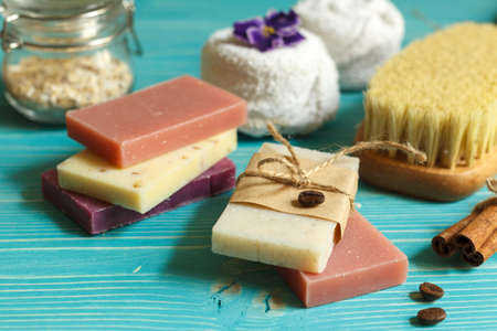 Spa lifestyle with colored natural soap, towels and a dry massage brush. On a blue wooden background