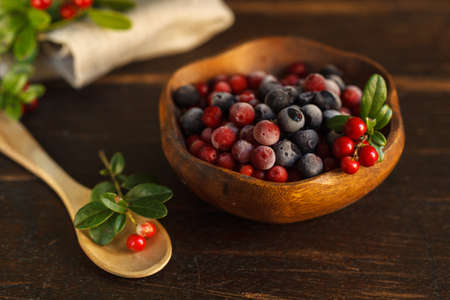 frozen cranberries and blueberries in a wooden bowl, decorated with a sprig of fresh cranberries