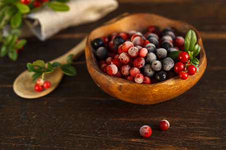 frozen cranberries and blueberries in a wooden bowl, decorated with a sprig of fresh cranberries.on a dark wooden background. Close-up, blurred background