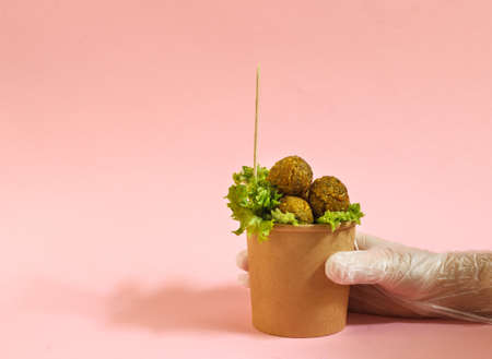 A hand in a protective glove holds a paper Cup with a portion of falafel. The concept of takeout. On a pink background with space for text