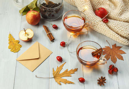Two cups of fragrant tea with rose hips and spices on light boards, with a garland, apples and dry leaves