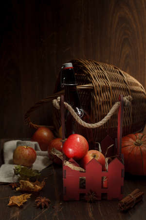 Composition with apples in a wooden decorative box and a bottle of cider. Low key, on a wooden background, copy space