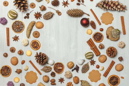 Christmas background of cones, cinnamon, nuts, spices, cookies on light boards. In the center there is free space for text in the form of a circle