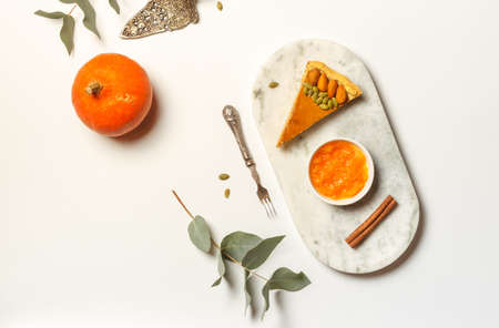 A slice of pumpkin pie on a marble stand with cinnamon and pumpkin jam. On a white table with a dessert fork and green leaves