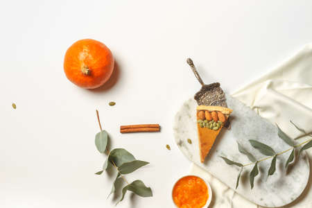 Layout with a piece of pumpkin pie, small pumpkin and green leaves on a white background. Horizontally with space