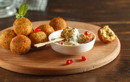 A portion of falafel, a vegetarian lean dish of ground chickpeas, is served with sesame tahini sauce. Fast street food with health benefits