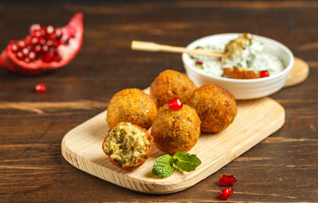 falafel, chickpea balls on a wooden Board with sauce and pomegranate seeds. Close-up on a dark wooden table Stock Photo