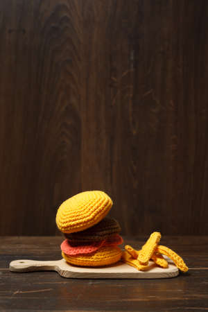Toy hamburger amigurumi and French fries on a wooden board. Toy, knitted food. On a dark wooden background, vertically, with space Фото со стока