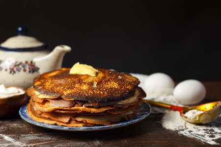 A stack of pancakes with a slice of butter, a teapot of tea in the background, and baking ingredients. Close-up, selective focus