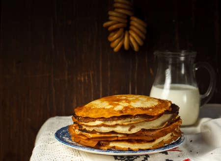 A stack of pancakes on a plate, a jug of milk, and a bunch of driers in the background. Low key, dark wood background, with space