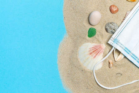 The concept of a vacation, trip to the sea in the new conditions of the global pandemic. Sand with shells and sea pebbles and a protective mask on a blue background. Top view with space Stock Photo