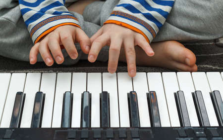 The child learns a new melody.Children's hands on the keys of the synthesizer. Homeschooling.Music classes. Close-up, selective focus 版權商用圖片