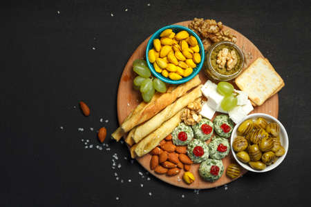 Assorted snacks for wine or beer on a wooden round tray. On a black background, overhead, a copy of the space Фото со стока