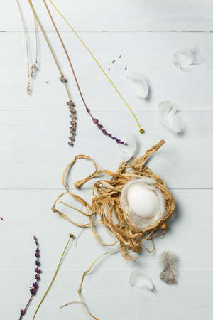An egg in a nest of straw and feathers. Top view on a light gray wooden background. Vertically with space