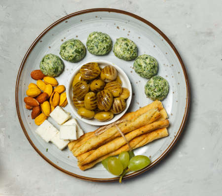 A plate of tapas in close-up, overhead, grey background.Dried olives, pistachios with saffron ,breadsticks and cheese balls with herbs. Фото со стока