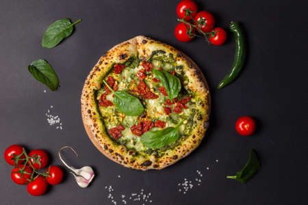 Pizza with dried tomatoes, pesto sauce, garlic and chili pepper. Spicy pizza. National, Italian, American, Neapolitan cuisine