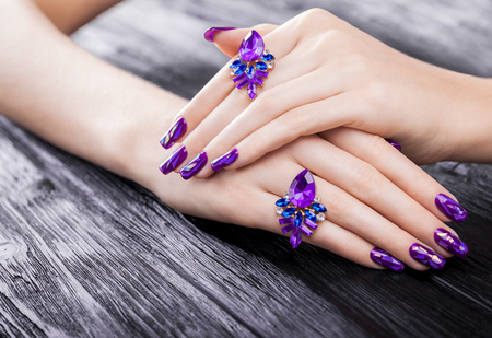 Shattered glass purple manicure on black wooden background 免版税图像 - 93132098
