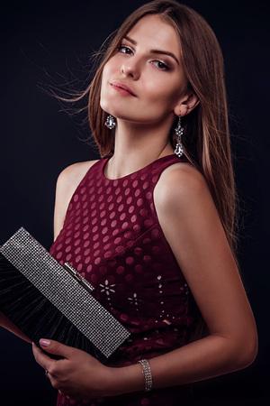 黒い背景にハンドバッグを持つ長い髪を持つ美しい女性 写真素材