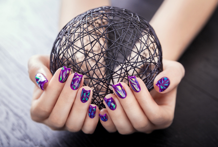 SWoman with shattered glass purple manicure holds a ball on black wooden background