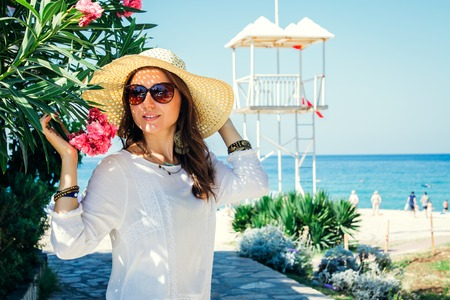 Young pretty woman walking on the beach by the rhododendron flowers Stock Photo