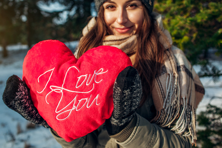 Young woman holds a red pillow heart with a writing in winter forest