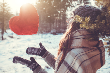 Young woman throws a red pillow heart in winter forest at sunset
